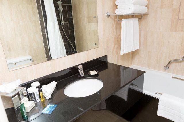 ترفق غرف تقرير عن فندق هيلتون اولمبياد لندن بحمامات أنيقة من الغرانيت ومزودة بأدوات الاستحمام المجانية